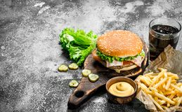 Street food. Burger with fries, sauce and cola. On a rustic background Stock Images