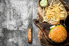 Street food. Burger with fries and sauce. On a rustic background Stock Photo