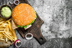 Street food. Burger with fries and sauce. On a rustic background Royalty Free Stock Image