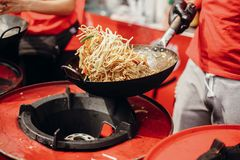 Street food chef cooking noodles and vegetables in a pan on fire at open kitchen. Fried noodles in a wok on the open fire. Asian stock images