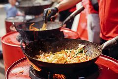 Street food chef cooking noodles and vegetables in a pan on fire at open kitchen. Fried noodles in a wok on the open fire. Asian royalty free stock photography