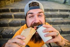 Street food concept. Man bearded eat tasty sausage and drink paper cup. Urban lifestyle nutrition. Junk food. Carefree. Hipster eat junk food while sit stairs royalty free stock photos