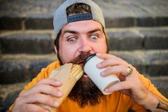Street food concept. Man bearded eat tasty sausage. Urban lifestyle nutrition. Junk food. Carefree hipster eat junk food. While sit stairs. Guy eating hot dog stock photo