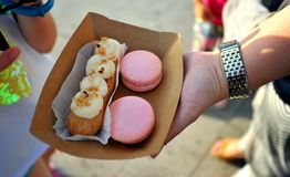 Street food in Constanta , Romania. With eclair and pink macarons . fresh french cookies on the streets of the city stock photography