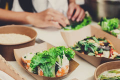 Street food festival, delivery, catering service. Street food festival, catering service. Vegetable salads in kraft paper plates sold outdoors at local market Royalty Free Stock Images