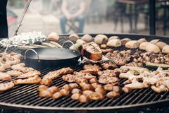 street food festival. grilled meat and vegetables mushrooms. roasting beef pork on big grill, open kitchen, food court. cooking s stock images