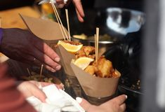 Street food festival. Fish and chips with hands of event guests stock photos