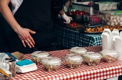 Street food festival.  salads in plastic boxes, man cooking fast. Food take to go. chef in form and gloves at open kitchen outdoors, catering. summer picnic Royalty Free Stock Photos