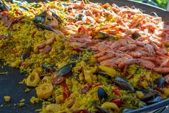 Street food in France, fresh prepared paella with rice and sea food in big pan on street market, ready to eat. Street food in France, fresh prepared colorful stock images