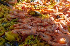 Street food in France, fresh prepared paella with rice and sea food in big pan on street market, ready to eat. Street food in France, fresh prepared colorful stock image