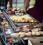 Street food, fried potatoes, meat on the grill. In roasting process royalty free stock photos
