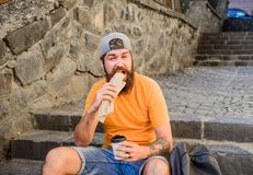 Street food so good. Urban lifestyle nutrition. Carefree hipster eat junk food while sit on stairs. Hungry man snack. Junk food. Guy eating hot dog. Man stock images