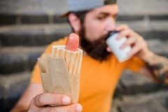 Street food so good. Urban lifestyle nutrition. Carefree hipster eat junk food while sit on stairs. Hungry man snack. Junk food. Guy eating hot dog. Man royalty free stock photography