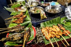 Traditional grilled fish and chicken sticks. Street food, Laos.