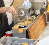 Making donuts. Demo cooking. Street food market. Vendors at the street market make fresh donuts. Small donut manufacture at street market. Demonstration cooking Royalty Free Stock Image