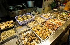 Street food at night in Vietnam. Delicious seafood for tourist at street market. Fresh shells and musles assortment. stock image