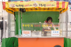 Street food is one of tourist attraction in Seoul. Seoul, South Korea - APRIL 25, 2016: A lady grills and cook seafood dishes for customers at her stall in Stock Images
