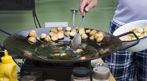 Street food, potatoes fried in oil. In roasting process stock photos