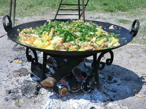Street food - potatoes with meat and vegetables fried on fire Royalty Free Stock Photos
