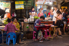 Street food restaurant in Bangkok. BANGKOK, THAILAND, February 18, 2015 : Some customers are sitting at the restaurant tables in a street of Chinatown in Bangkok Royalty Free Stock Photography