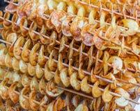 Street food. Spiral potato chips on a sticks stock photo
