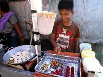 A street food vendor cooks snack items in his food cart. ANTIPOLO CITY, PHILIPPINES - APRIL 24, 2017: A street food vendor cooks snack items in his food cart. A stock images