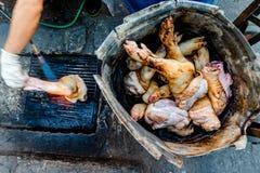Street food vendor is grilling pork legs using blowtorch. stock photos