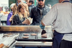 Street food vendor grills burgers for customers. Stock Photo