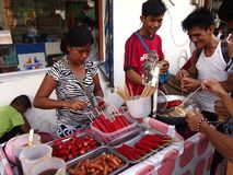 A street food vendor sells a variety of street food stock images