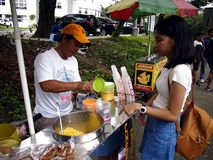 A street food vendor serves sweet corn to a customer. royalty free stock image