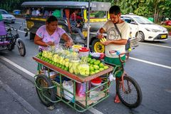 A street food vendor slices fresh green mango which sells on foo stock photo