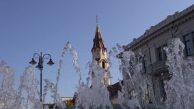 Street fountain and old orthodox st Nicholas church tower in Vilnius Royalty Free Stock Photo