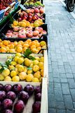 Street fruit market of peaches and plums in summer Italy. Street fruit market. Different sorts of fresh ripe plums, peaches and grapes in wooden boxes along the royalty free stock image