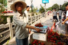 Street fruit seller is pointing to scale & weight Stock Photos