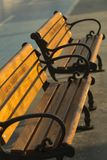 Close-up of a couple of wooden ironcast street benches under morning sun with a bicycle lane in the background. royalty free stock image