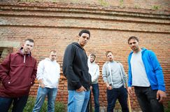 Street gang. Portrait of several street hooligans or rappers on background of brick wall Royalty Free Stock Image