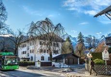 A street in Garmisch-Partenkirchen town in Bavarian Alps. Garmisch-Partenkirchen, Germany, January 10, 2015: small Alpine town street, a stranger and a ski bus Royalty Free Stock Photos