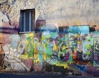 street graffiti art murals on old grunge wall with single window in old center of Odessa, Ukraine Stock Photos