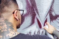 Street graffiti artist painting with a color spray can a dark monster skull graffiti on the wall in the city outdoor royalty free stock image