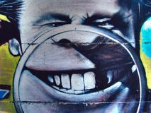 Street graffiti on the public wall caricature head of a man with magnifying glass and teeth. Novi sad Serbia 08.14.2010.  Stock Image
