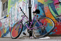 Street graffiti wall parked damaged wheel bycicle. Street coloured graffiti on wall and parked damaged bycicle on sidewalk in a typical american city Stock Photos