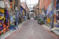 Street with graffiti on the walls Stock Photos
