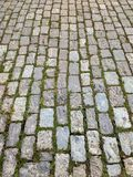 Street of granite stones in perspective, with weeds. stock image