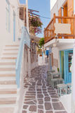 Street of Greek island with stairs, flowers and street cafe. Stock Photography