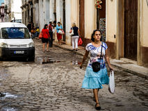 Street of Havana, Cuba. Havana, Cuba - January 5, 2016: Typical scene of one of streets in the center of La Havana - colonial architecture, cars and people Stock Images