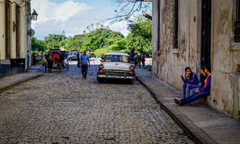 Street of Havana, Cuba. Havana, Cuba - January 5, 2016: Typical scene of one of streets in the center of La Havana - colonial architecture, cars and people Royalty Free Stock Images