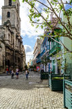 Street of Havana, Cuba. Havana, Cuba - January 5, 2016: Typical scene of one of streets in the center of La Havana - colonial architecture, people walking around Royalty Free Stock Photo