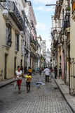 Street of Havana, Cuba. Havana, Cuba - January 5, 2016: Typical scene of one of streets in the center of La Havana - colonial architecture,  and people walking Stock Photos
