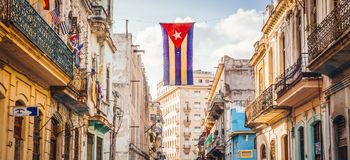 Street in Havana with Cuban Flag. A cuban flag with holes waves over a street in Central Havana. La Habana, as the locals call it, is the capital city of Cuba Stock Photo