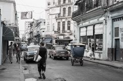Street in Havana with people walking to and fro, classic American vehicles and old dilapidated buildings. HAVANA CUBA - JULY 8 2012; Street in Havana with people stock image